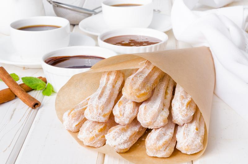 Baked churros with cinnamon, powdered sugar, chocolate and caramel sauce. Spanish cuisine royalty free stock photo
