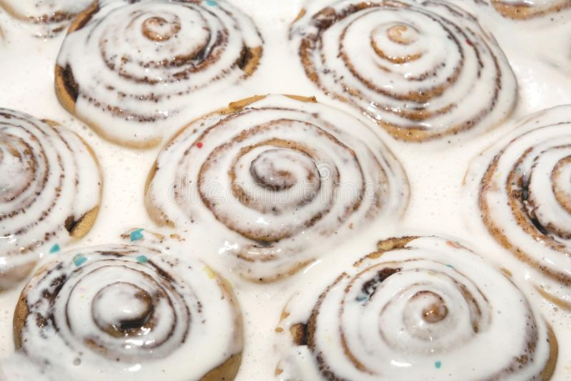Baked cinnamon buns were poured over with a white icing to soak royalty free stock photography