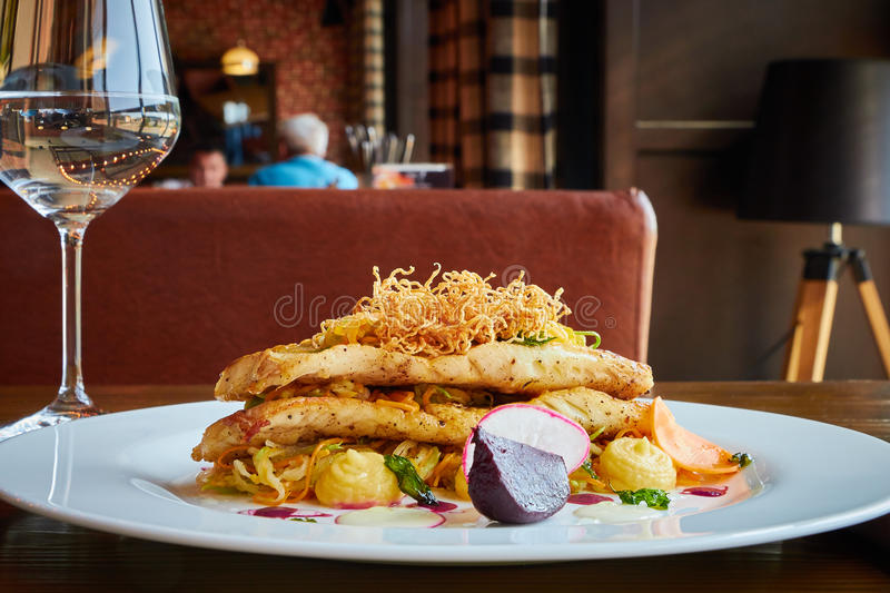 Baked cod fillet with vegetables in restaurant interior royalty free stock images