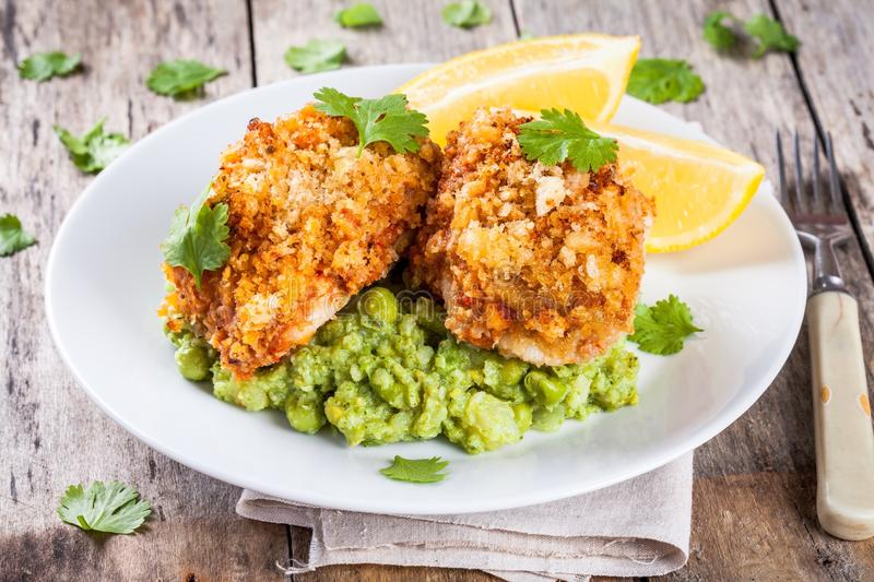 Baked cod fish in breadcrumbs with mashed green peas and broccoli royalty free stock photo