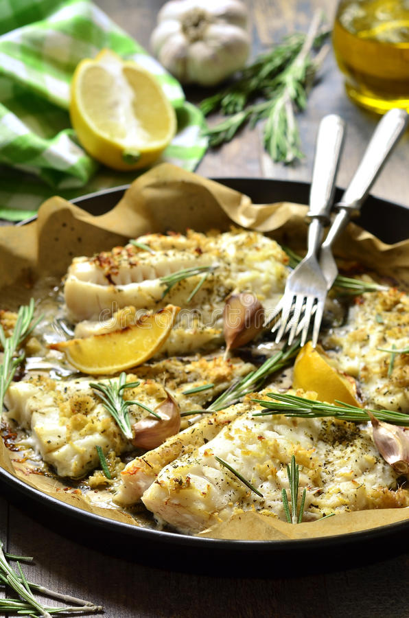 Baked cod with ginger,lemon and rosemary. Baked cod with ginger,lemon and rosemary on a tray royalty free stock photo