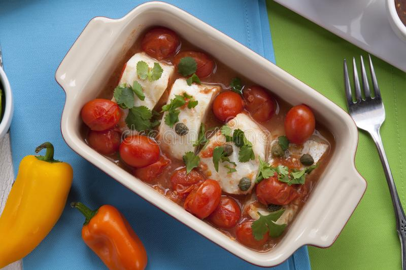 Baked Cod With Tomatoes. Mexican style baked cod with cherry tomatoes. Garnished with mexican condiments: guacamole, spicy salsa, marinated hot pepper, grilled royalty free stock photos