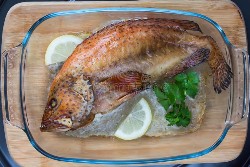 Baked coral grouper with lemon and green celery in a glass tray. On wooden cutting board, top view stock image