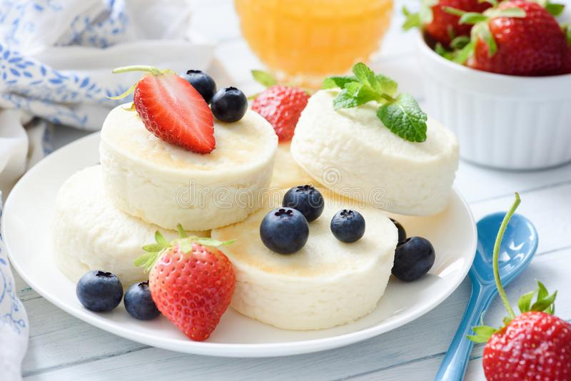 Baked cottage cheese cheesecake or syrniki with berry fruits. Healthy summer dessert stock photo