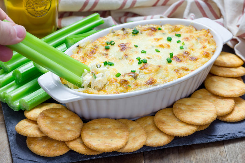 Baked crab dip, served with celery sticks and crackers royalty free stock photography