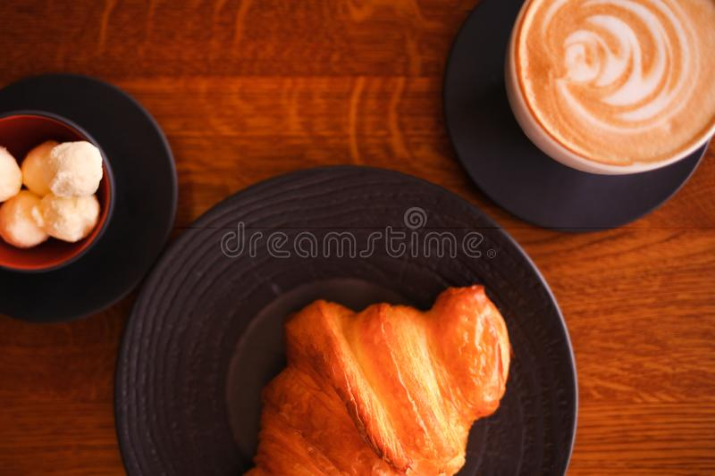 Baked croissant on a black plate with a white coffee cup and butter. Bakery restaurant lifestyle. stock image