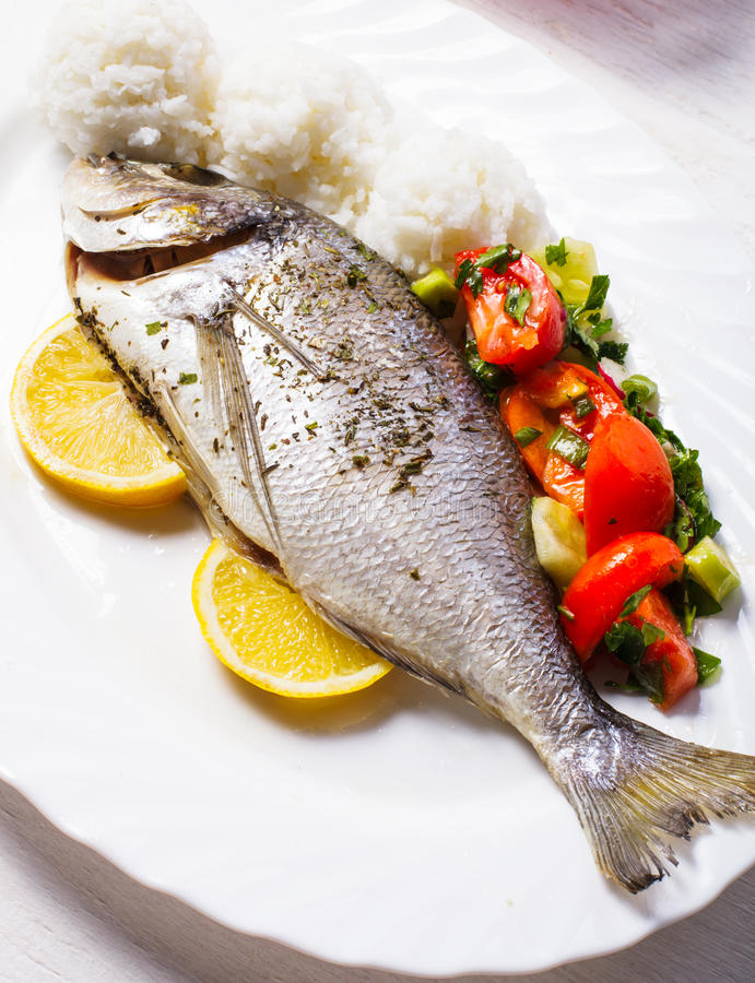 Baked dorado fish. With rice and salad on the white plate royalty free stock photo