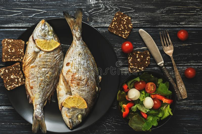 Baked Dorado fish on a black plate, salad with tomato mozzarella and lettuce leaves. royalty free stock image
