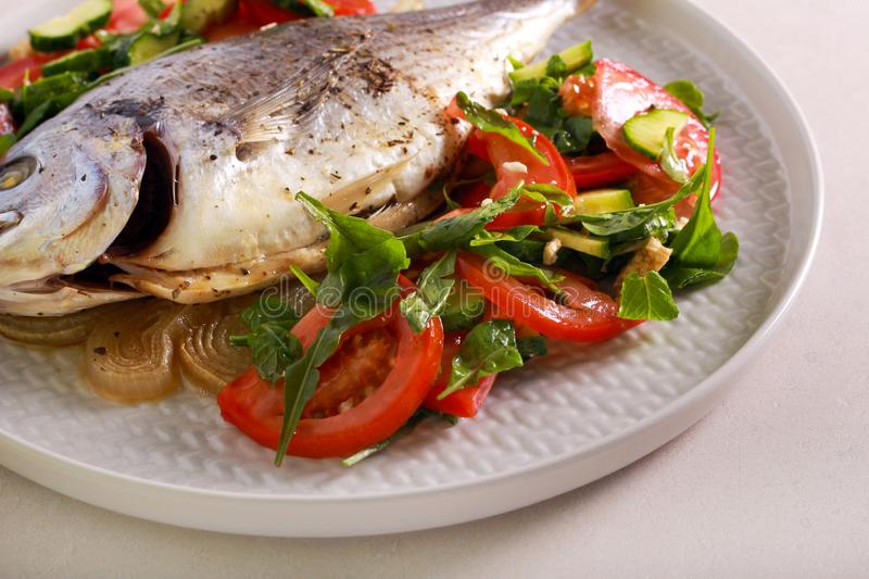 Baked dorado fish served with salad. On plate stock photo