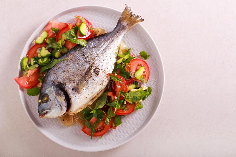 Baked dorado fish served with salad. On plate stock images