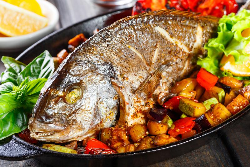 Baked dorado fish with vegetables and lemon on pan on wooden background close up. royalty free stock photo