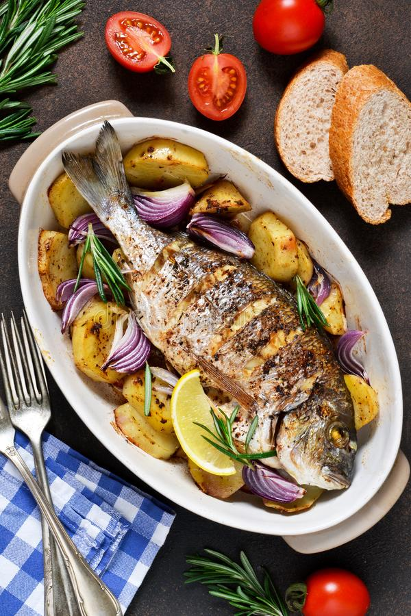 Baked dorado with Provencal herbs and potatoes.  royalty free stock image
