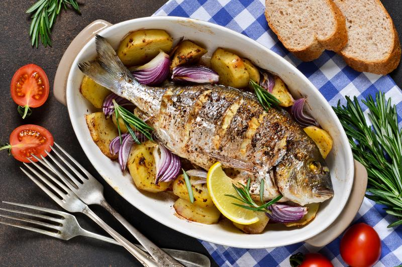 Baked dorado with Provencal herbs and potatoes.  stock images