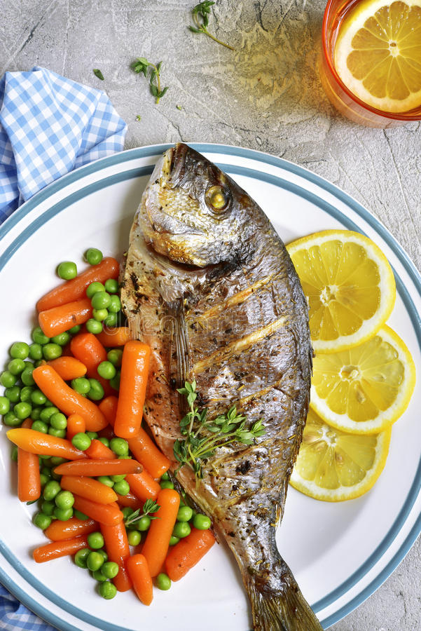 Baked dorado or sea bream with spring vegetables.Top view. royalty free stock images