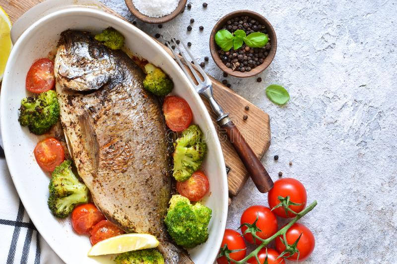 Baked dorado with spices, with broccoli and tomatoes. On a concrete background stock photo