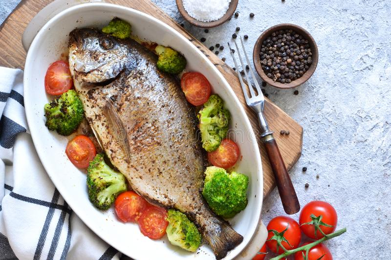 Baked dorado with spices, with broccoli and tomatoes. On a concrete background stock images