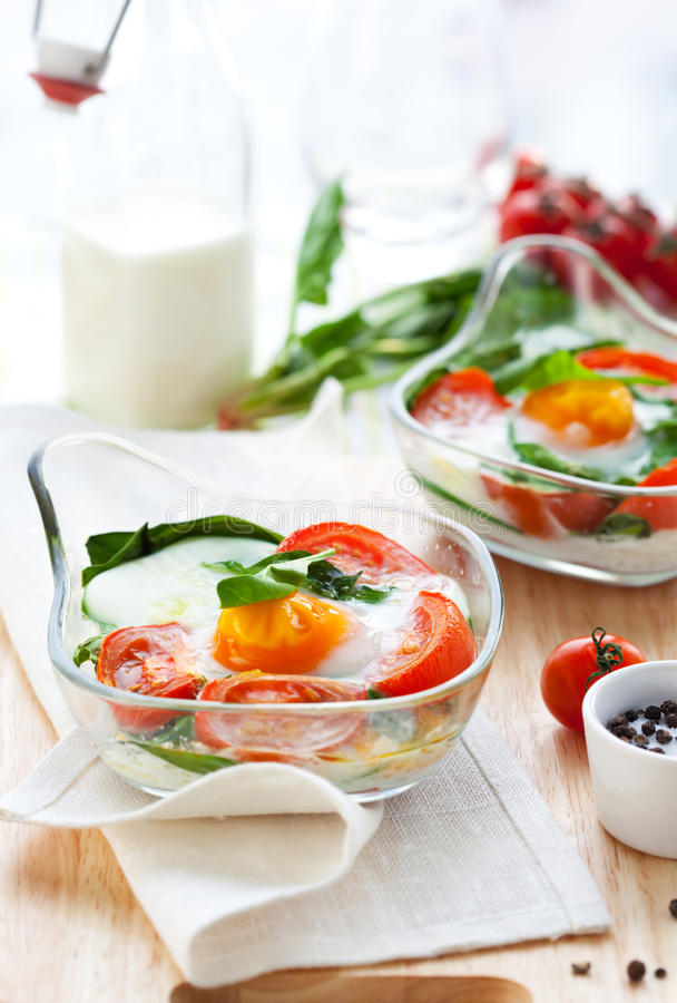 Baked egg with tomatoes and spinach royalty free stock photography