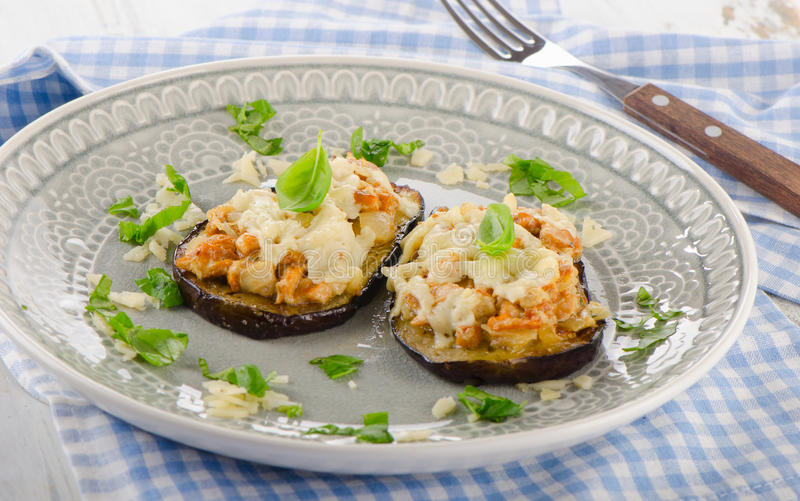 Baked eggplant with chanterelles, cheese and basil. stock image