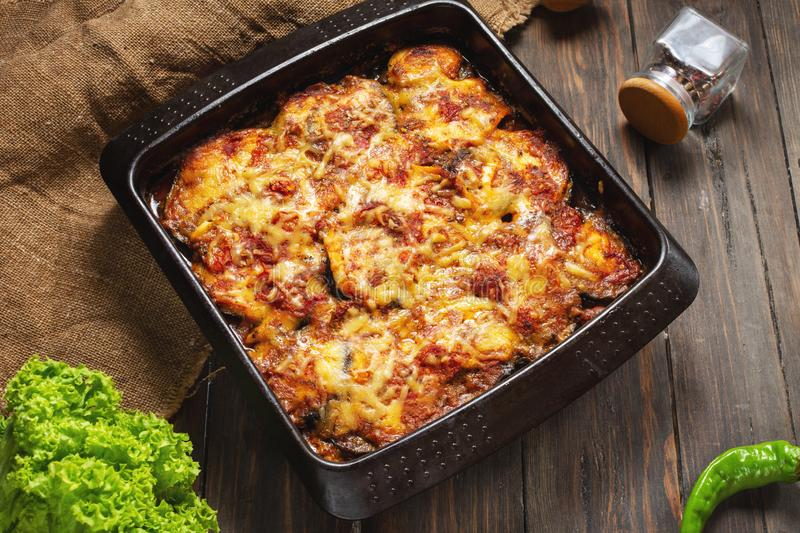 Baked eggplant with cheese on a wooden table. Parmigiana melanzane. Italian cuisine. stock image
