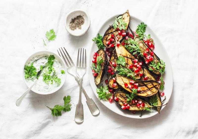 Baked eggplant with feta, greek yogurt, cilantro sauce and pomegranate seeds on light background, top view. Delicious snack, tapas. Appetizers royalty free stock images