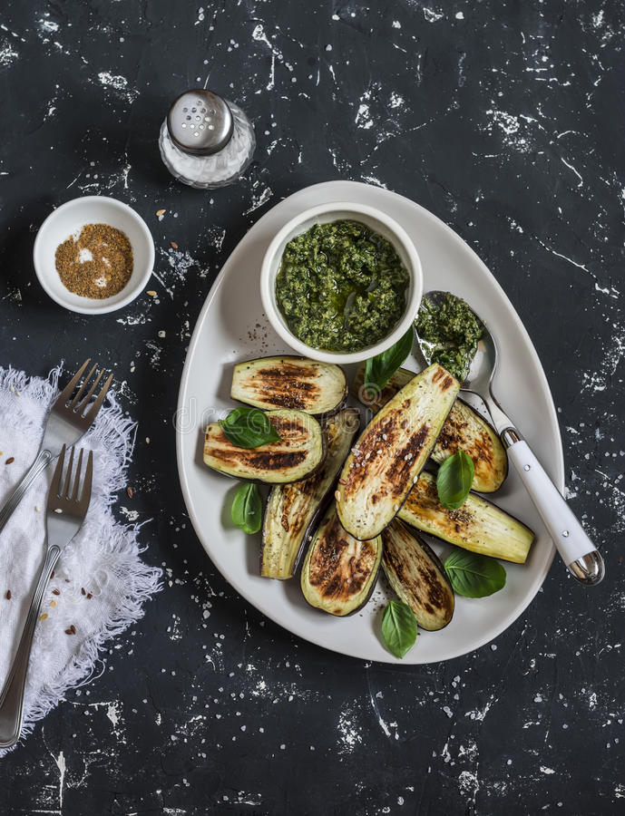 Baked eggplant and pesto sauce. On a dark background stock photography
