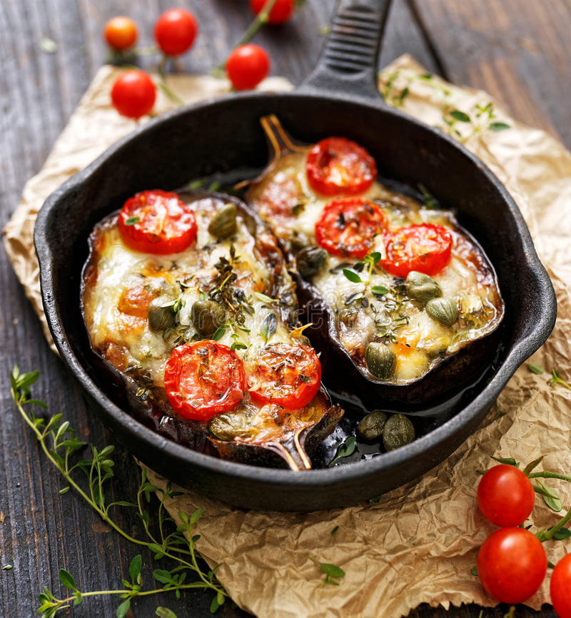 Baked eggplant stuffed with vegetables and mozzarella cheese with addition aromatic herbs. royalty free stock images
