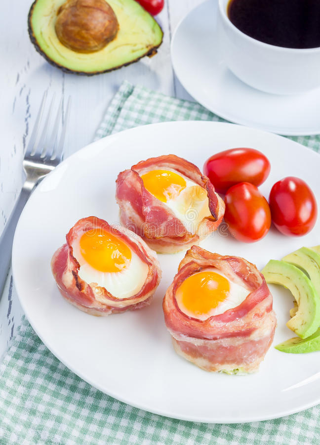 Baked eggs with avocado in bacon cups royalty free stock image