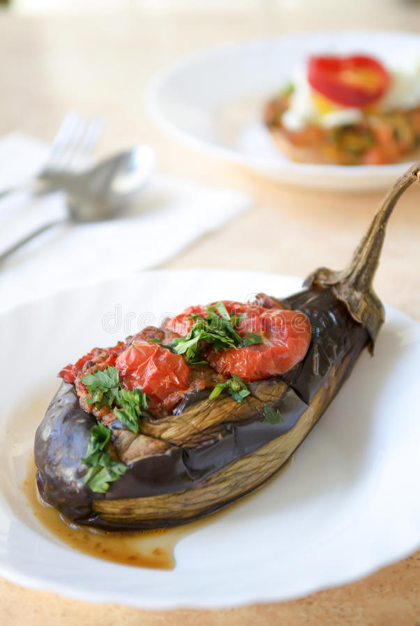 Baked encheu a beringela com tomates, alho e a beringela da paprika, alimento home romeno da culinária, fundo é forquilha e colhe fotos de stock