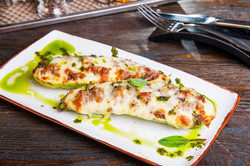 Baked füllte Zucchiniboote an Die Zucchini, die mit Fleisch- und Käse- und Pestosoße angefüllt wurde, diente auf der weißen Platt lizenzfreie stockfotografie