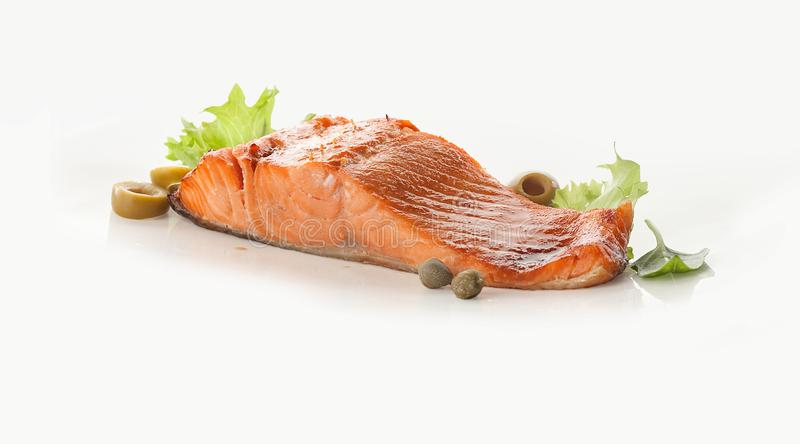 Baked fillet of salmon with olives, capers and lettuce. On the white royalty free stock photos