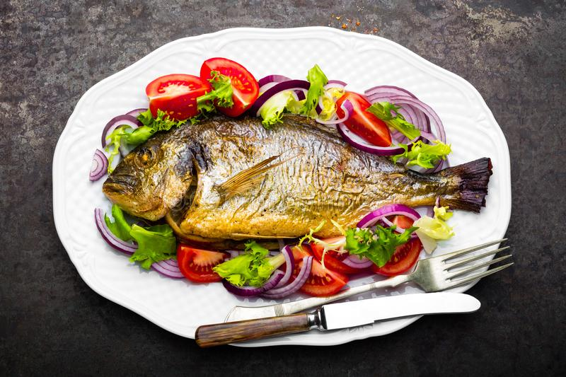 Baked fish dorado. Dorado fish oven baked and fresh vegetable salad on plate. Sea bream or dorada fish grilled and vegetable salad. Top view royalty free stock images