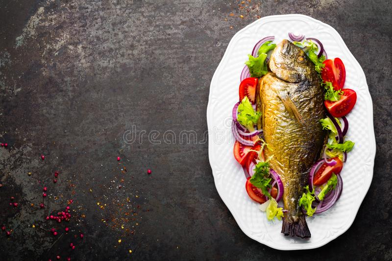 Baked fish dorado. Dorado fish oven baked and fresh vegetable salad on plate. Sea bream or dorada fish grilled and vegetable salad. Top view royalty free stock image