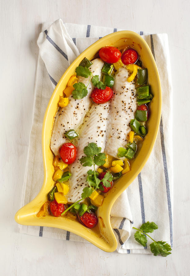 Baked fish fillet with tomatoes and sweet peppers royalty free stock photography