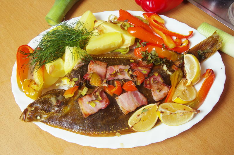 Baked fish flounder. With vegetable and bacon royalty free stock photo
