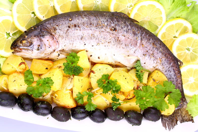 Baked Fish With Potatoes, Black Olives, Salad And  Lemon Royalty Free Stock Photography