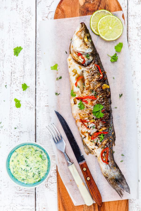 Baked fish sea bass with lime and parsley royalty free stock image