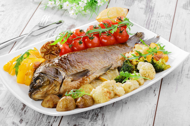 Baked fish with vegetables stock photos