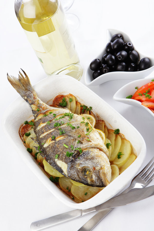 Baked gilt-head sea bream. With vegetables and white wine stock photography