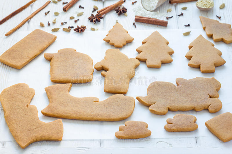 Baked gingerbread cookies for christmas 3D composition on wooden table, spices on background royalty free stock photo