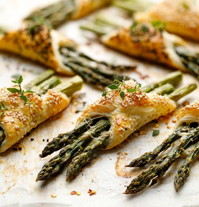 Baked green asparagus in puff pastry sprinkled with sesame seeds, nigella seeds and fresh thyme on a white background, close-up, t stock images