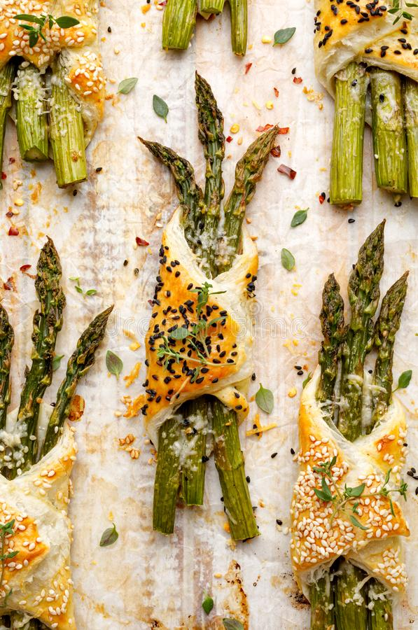 Baked green asparagus in puff pastry sprinkled with sesame seeds, nigella seeds and fresh thyme on a white background, close-up, t stock photos