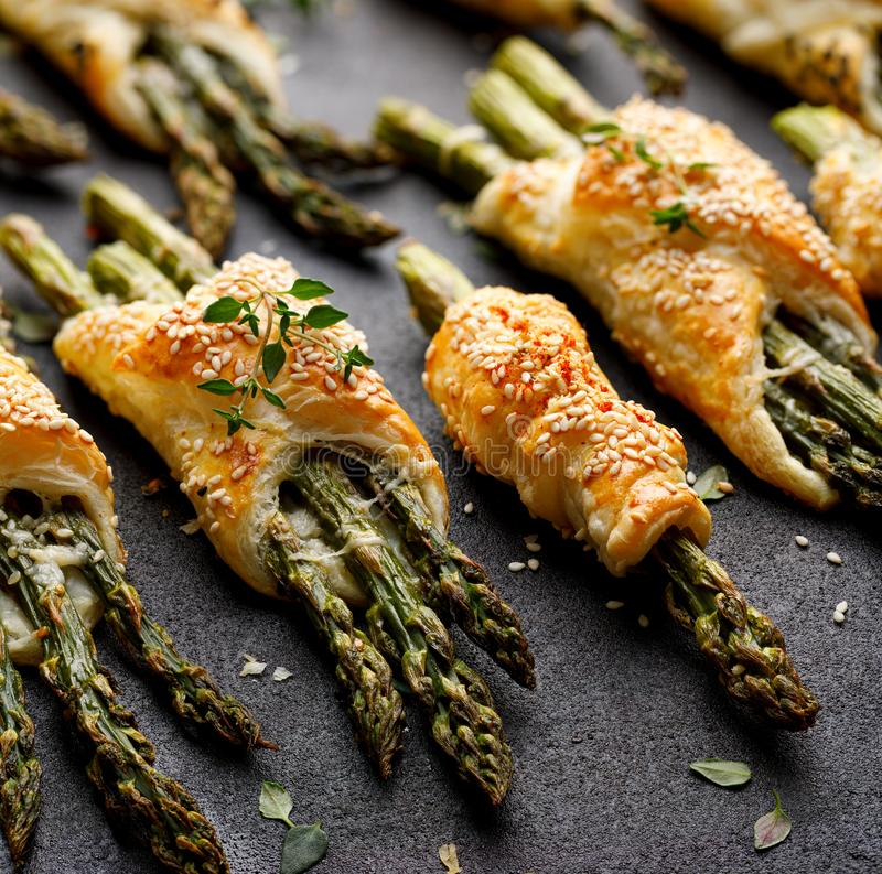 Baked green asparagus in puff pastry sprinkled with sesame seeds, nigella seeds and fresh thyme on a black background, close-up, t stock photography