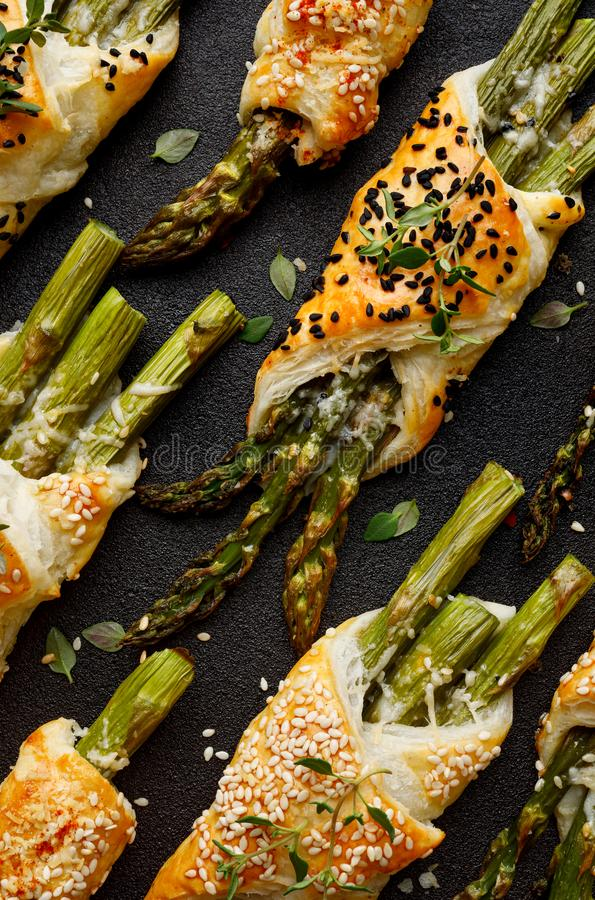 Baked green asparagus in puff pastry sprinkled with sesame seeds, nigella seeds and fresh thyme on a black background, close-up, t stock image