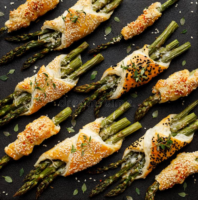 Baked green asparagus in puff pastry sprinkled with sesame seeds, nigella seeds and fresh thyme on a black background, close-up, t stock photo