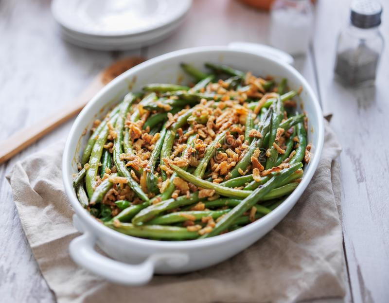 Baked green bean casserole topped with french fried onions stock images