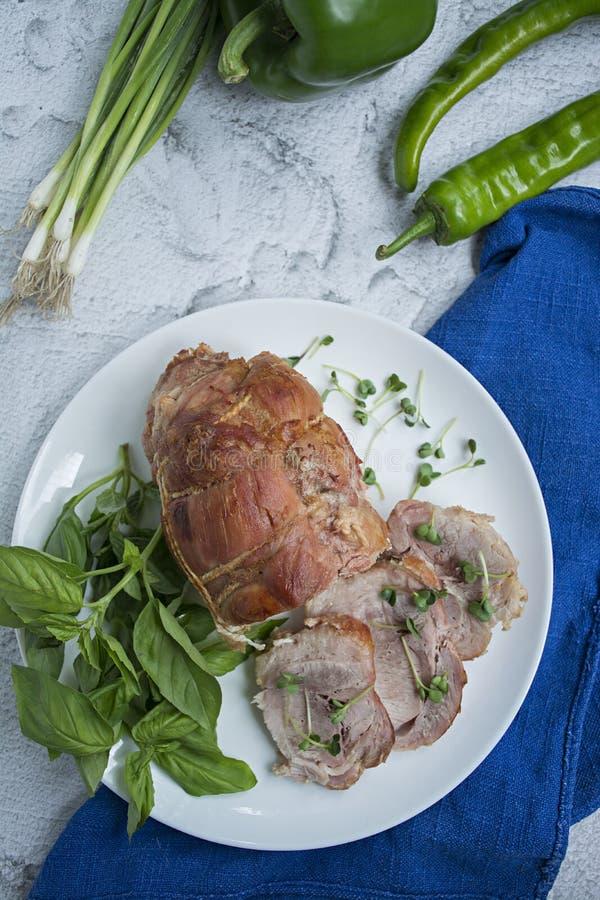 Baked ha farcito il rotolo della carne di maiale con i verdi servito su un piatto bianco Fondo leggero fotografia stock
