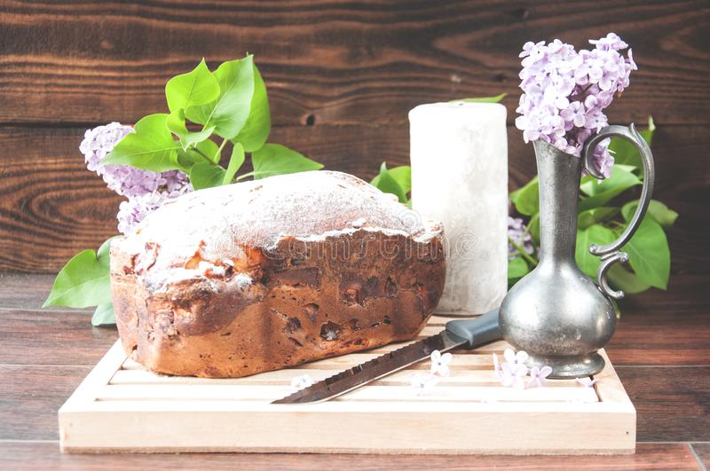 Baked homemade cake dusted with powder stands on a white plate near the lilac flowers stock images