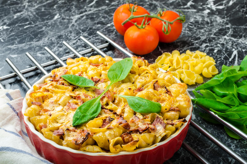 Baked homemade pasta with leeks, bacon and cream. Spinach and fresh tomatoes from the garden royalty free stock photography