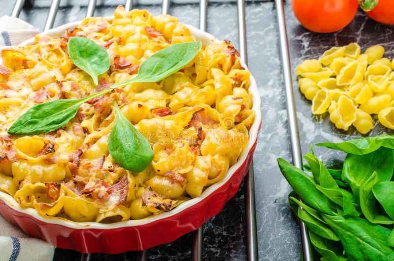 Baked homemade pasta with leeks, bacon and cream. Spinach and fresh tomatoes from the garden stock images