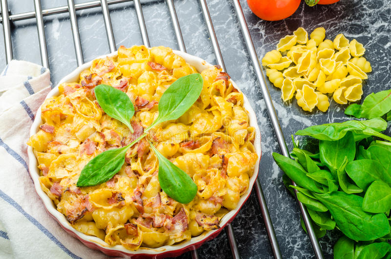 Baked homemade pasta with leeks, bacon and cream. Spinach and fresh tomatoes from the garden royalty free stock photos